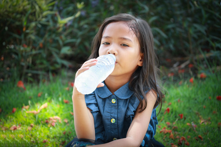 tomando agua: Ni�a asi�tica bebe agua mineral. Foto de archivo