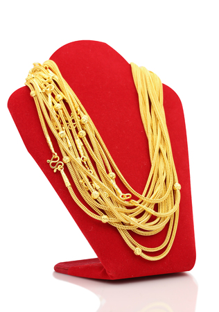 Gold necklaces on necklace display stand white background.