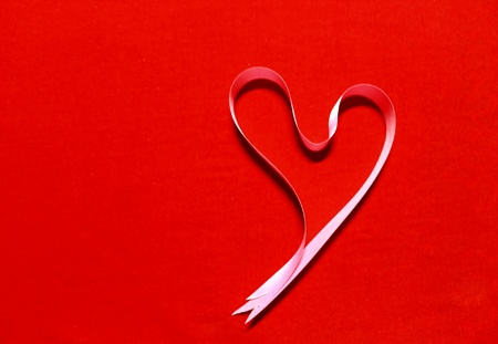 Heart from pink ribbon on red background