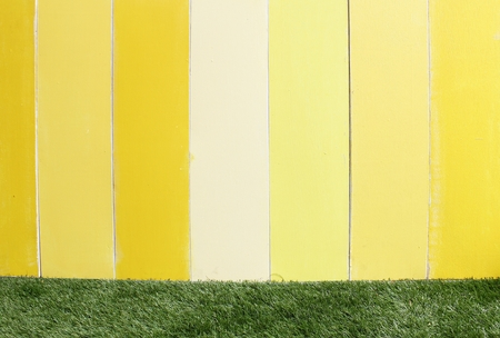 Yellow wooden wall and grass
