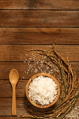 Jasmine rice in wood bowl and paddy rice on a brown wooden background beautiful Thai food