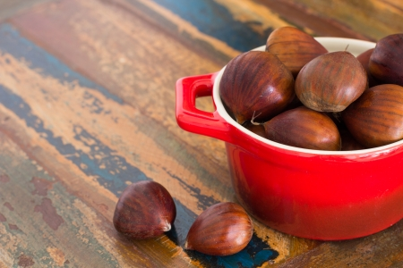Fresh chestnut in red bowl on wooden table photo