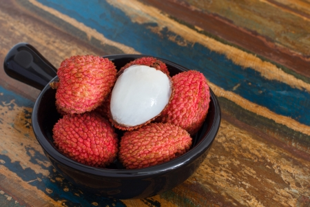 Lychee in black bowl on a wooden table