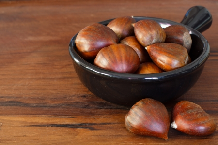 Chestnut in black bowl on wooden table photo