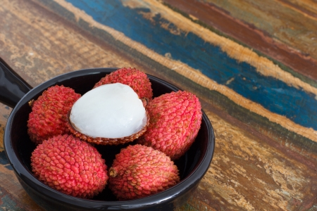 Lychee in black bowl on a wooden table photo