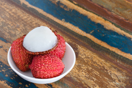 Lychee on white plate on wooden table photo