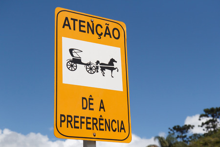 sky is the limit: Yellow and black horse road sign with blue sky background in Brazil Stock Photo