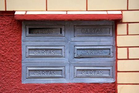 Old postboxes on red white wall in Brazil photo