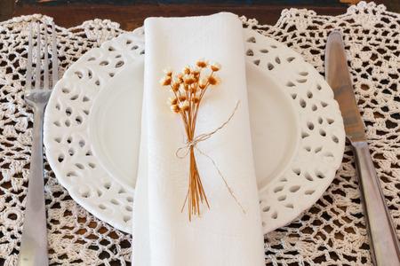 servilleta de papel: Decoraci�n de la tabla con placas, servilleta, tenedor, cuchillo y flores secas Foto de archivo