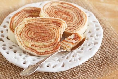 Brazilian dessert Bolo de rolo  swiss roll, roll cake  on white plate spoon sackcloth  Selective focus