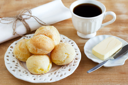 Brazilian snack pao de queijo  cheese bread  on white plate butter cup of coffee on wooden table  Selective focus  Archivio Fotografico