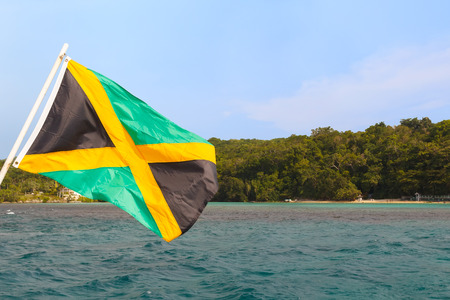 kingston: Jamaica flag waving sea beach sky  Selective focus on flag