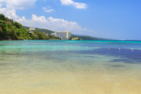 Beach turquoise transparent caribbean sea blue sky white clouds, Jamaica photo