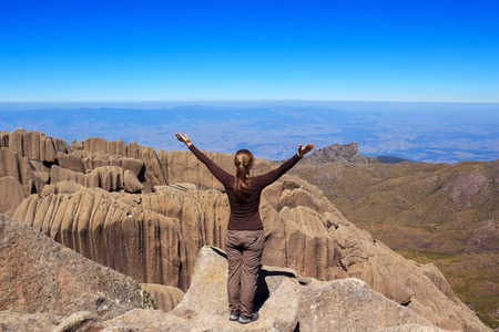 Young woman on edge of the mountain Ahulhas Negras looking at horizon, Brazil photo