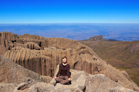 Young smiling woman sitting on edge of the mountain Ahulhas Negras yoga pose with closed eyes, Brazil photo