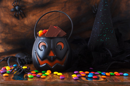 Sweets chocolate candy for Halloween, witch hat, spider, web. Selective focus photo
