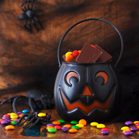 Sweets chocolate candy for Halloween in pumpkin bowl, spider, web. Selective focus photo