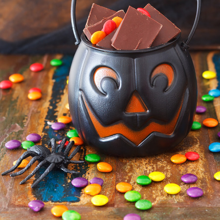 Halloween Sweets chocolate candy in pumpkin bowl, spider. Selective focus photo