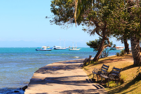 armacao: Benches on embankment with view to sea with boats, yachts in Armacao dos Buzios near Rio de Janeiro, Brazil Stock Photo