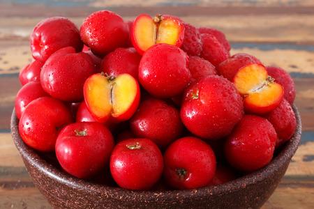 Red acerola - malpighia glabra, tropical fruit  in wicker busket. Selective focus