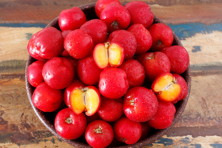 Red acerola (malpighia glabra), tropical fruit  in busket. Selective focus. Imagens