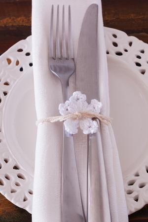 serviette: Christmas decoration: White plate serviette fork knife with  white crochet snowflake. Selective focus Stockfoto