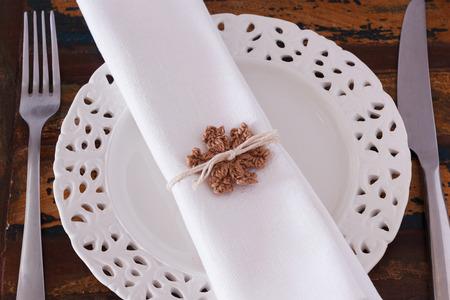 serviette: Kerstversiering: Witte plaat servet vork mes met bruine gehaakte sneeuwvlok. Selectieve aandacht