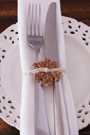 servilleta de papel: Decoraci�n de Navidad hecha a mano: Blanco plato servilleta tenedor cuchillo con marr�n crochet copo de nieve. Enfoque selectivo