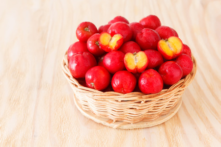 tropical fruits: Red acerola - malpighia glabra, tropical fruit  in wicker busket with copy space. Selective focus