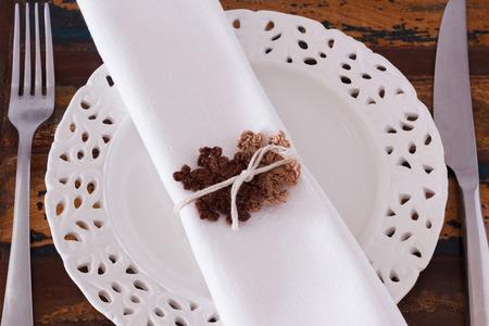 servilleta de papel: Decoraci�n de Navidad: Placa blanca servilleta tenedor cuchillo con dos copos de nieve de crochet marrones. Enfoque selectivo Foto de archivo