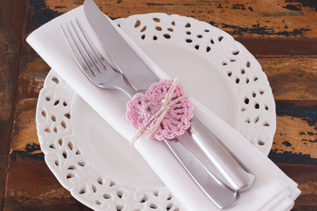 serviette: White plate serviette fork knife with handmade pink crochet heart for Saint Valentine Stock Photo