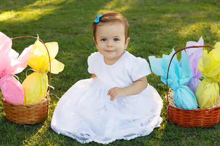 baby girl: Cute smiling baby girl on green grass with wicker basket with chocolate eggs for Easter holiday in park. Selective focus Stock Photo