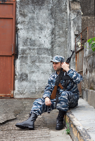 Caucasian military man with black sunglasses in urban warfare sitting with rifle protecting gate