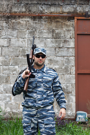 guerrilla: Caucasian military man with black sunglasses in urban warfare holding rifle on shoulder. Selective focis Stock Photo