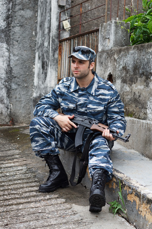guerrilla: Caucasian military man in urban warfare sitting and holding automatic weapon. Selective focus Stock Photo