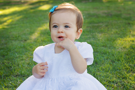 Cute happy little baby girl in white dress scratching first teeth in park on green grass. Selective focus