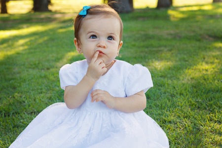 first teeth: Cute happy little baby girl in white dress scratching first teeth in park on green grass. Selective focus