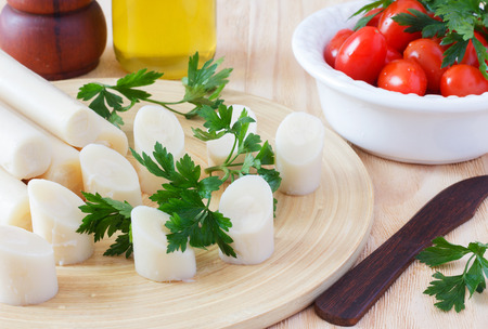 Cutting heart of palm (palmito) with cherry tomato on plate, olive oil and parsley with wooden knife. Selective focus photo