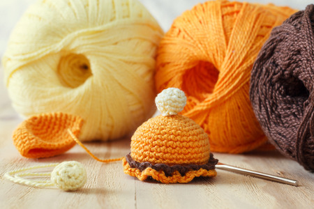 skein: Making of handmade colorful crochet toys sweets with skein on wooden table. Selective focus Stock Photo