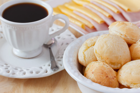 Brazilian snack pao de queijo (cheese bread) on white plate with cheese, ham, butter, cup of coffee on wooden table. Selective focus