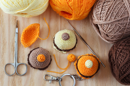 skein: Making of handmade colorful crochet toys sweets (key ring) with skein on wooden table. Selective focus Stock Photo