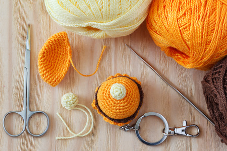 bibelot: Making of handmade colorful crochet sweets toys  (key ring) with skein on wooden table. Selective focus