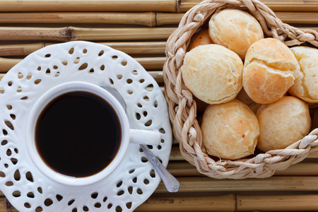 breakfast plate: Brazilian snack pao de queijo (cheese bread) on white plate with cup of coffee on bamboo table. Selective focus