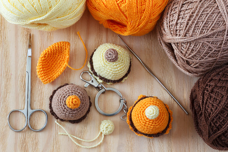 bibelot: Making of handmade colorful crochet toys sweets (key ring) with skein on wooden table. Selective focus Stock Photo