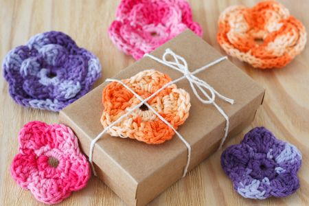 skein: Handmade colorful crochet flowers for decoration of gift with skein on wooden table. Selective focus
