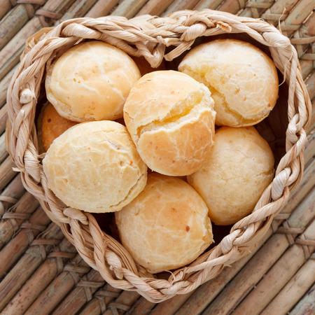 pao: Brazilian snack cheese bread (pao de queijo) in wicker basket on wooden table. Selective focus. Copy space