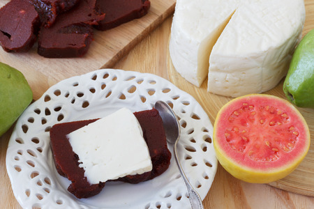 juliet: Brazilian dessert Romeo and Juliet of goiabada and Minas cheese on white plate with fresh goiaba on wooden table. Selective focus Stock Photo