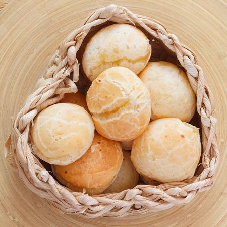 pao: Brazilian snack cheese bread (pao de queijo) in wicker basket on wooden table. Selective focus