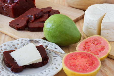 Brazilian dessert Romeo and Juliet on white plate, goiabada and Minas cheese with fresh goiaba on wooden table. Selective focus Stock Photo