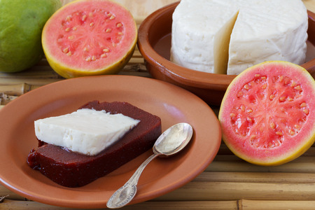 Brazilian dessert Romeo and Juliet of goiabada and Minas cheese with fresh goiaba on wooden table. Selective focus Archivio Fotografico
